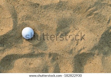 A golf ball on the sand ; top view - stock photo