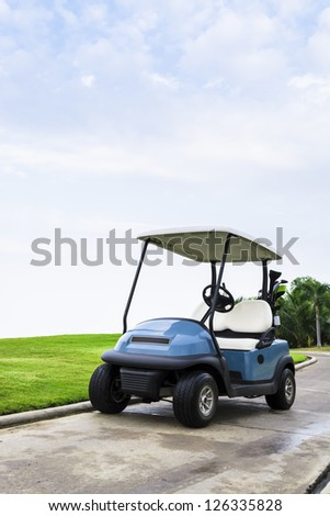 A golf cart with clubs on way to the Golf Course.