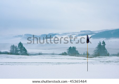 A golf course in Scotland on a snowy winter morning in December. View from a green with a blue flag, with trees, mist and mountains in the background.