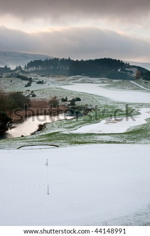 A golf course in Scotland on a snowy winter morning with warm morning light and clouds in the background.