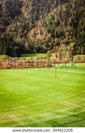a golf hole with a red flag pole on a beautiful vibrant golf course - stock photo