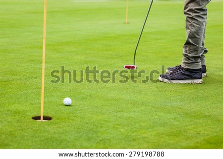 a golf player aiming for the hole on the green with a putter - stock photo