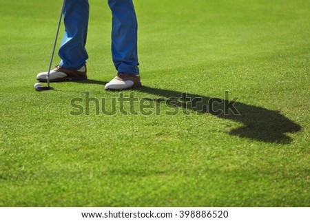 A golf player is preparing for his putting shot on a green - stock photo