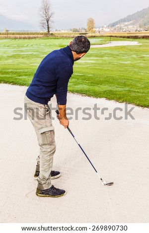 a golf player playing from a sand bunker on a beautiful golf course - stock photo