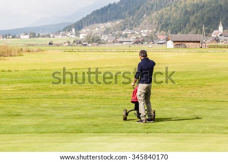 a golf player playing on a beautiful golf course and a golf bag full of golf clubs - stock photo
