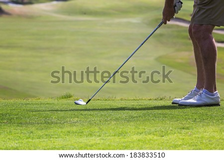 a golfer getting ready to hit the ball