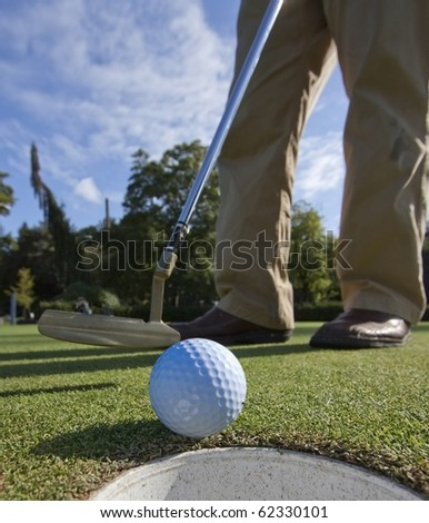 A golfer, having missed the putt by inches, has to tap in. - stock photo