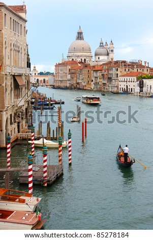 A gondola plows the Grand Canal with the Santa Maria Della Salute church in the background - stock photo