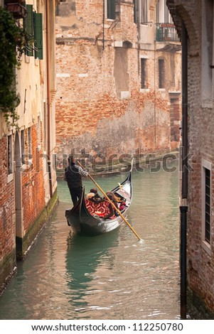 A gondola with tourists going down a small canal lined with urban houses - stock photo