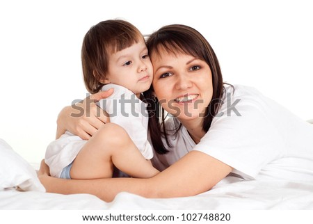 A good Caucasian mother with her daughter lying on the bed