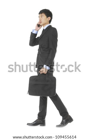 A good-looking asian businessman on the phone holding a laptop bag - stock photo