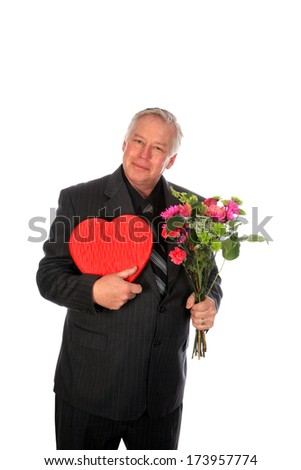 A good looking business man holds Valentine's Day Flowers and Chocolates in a red heart shaped gift box as a gift or gesture of love and affection. Isolated on white with room for your text. - stock photo