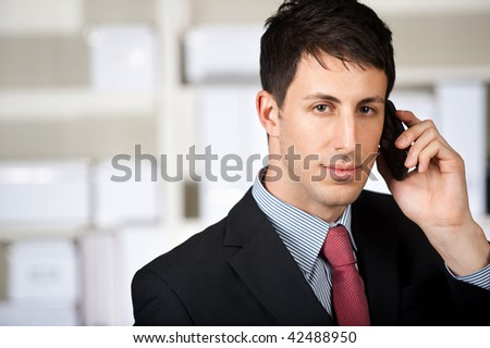 A good looking businessman using his mobile phone in the office