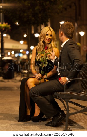 A good-looking couple talking on a bench in the city at night - stock photo