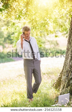 A good looking grey hair business man is standing naked feet in the grass, answering his phone.He is relaxing, his computer next to him, enjoying the shadow of the tree in a sunny day. - stock photo