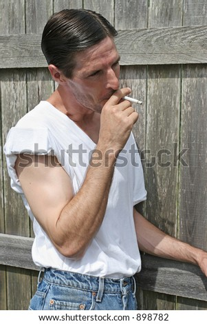 A good looking man smoking a cigarette outdoors.