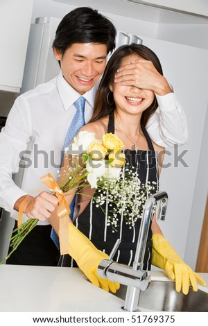 A good looking man surprising his wife with a bouquet of flowers at home - stock photo