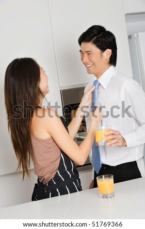 A good looking woman adjusting her husband's tie before he goes to work, at their home - stock photo