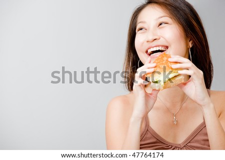 A good looking woman having a sandwich against white background