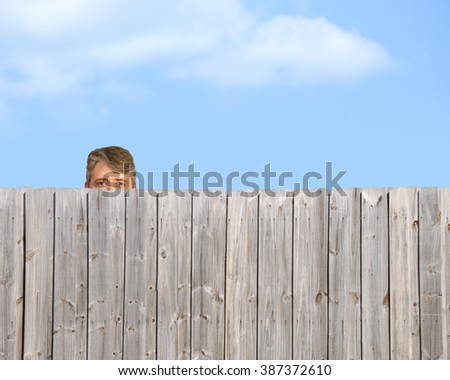 A goofy, happy man is being a peeping tom and nosy neighbor by stalking, watching and gawking over a wooden privacy fence - stock photo