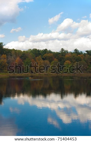 A gorgeous autumn scene with a lake and trees showing the bright colors of fall in New England. Kayakers enjoy the day in the distance. - stock photo