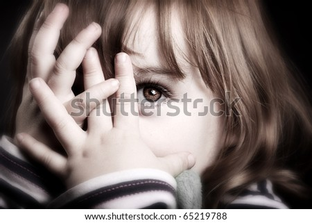 A gorgeous little girl playing peekaboo and peering through her fingers. Adorable.