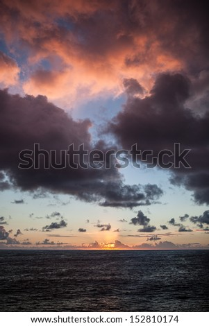A gorgeous sunrise lights up the clouds over the South Pacific Ocean. - stock photo