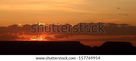 A gorgeous sunrise over Mather Point with clouds and a silhouette of the geological features at Grand Canyon National Park, Arizona, USA