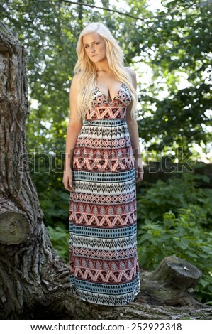 A gorgeous young blond model posing in a forest wearing a colorful dress on a sunny day near the beach. - stock photo
