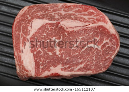 A gourmet Australian wagyu ribeye steak in a grill-pan, viewed from a high angle