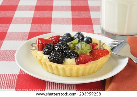 A gourmet fruit tart on a picnic table with a glass of milk