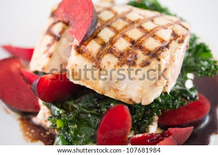 A gourmet healthy dinner of barbecued white sea bass atop a bed of kale and ricotta cheese dressed with fresh plums and balsamic vinaigrette. - stock photo