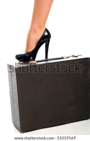 A graceful female leg in a black shoe on the black leather attache case