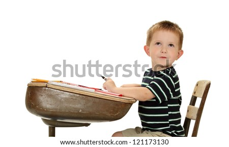 A grade school boy contemplates his next creative creation - stock photo