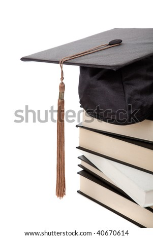 a graduation cap on top of a stack of books on a white background - stock photo
