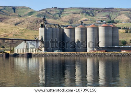 A grain elevator storage facility on a river - stock photo