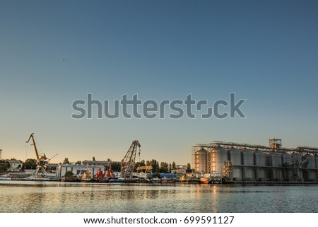 A granary in the port at sunset, port cranes near the water