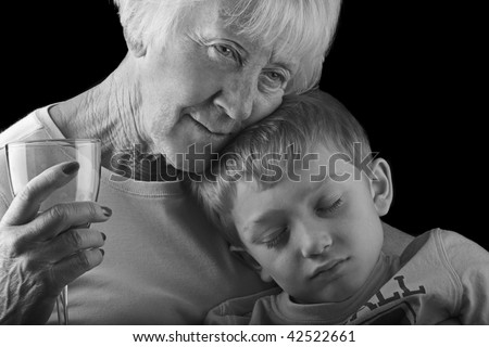 a grandchild sleeps while his grandmother cuddles him protectively