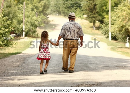 a grandfather with the granddaughter go on the road - stock photo