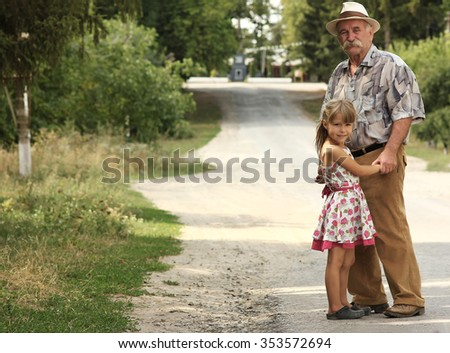 a grandfather with the grandson go on the road - stock photo