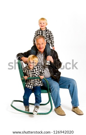 A grandfather with two boys in the studio on an isolated white background with a green rocking chair.