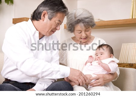 A grandma and a granddad babysitting their granddaughter - stock photo