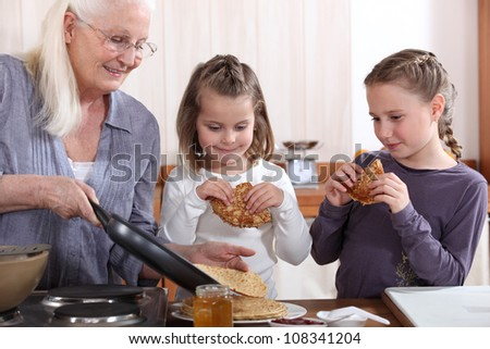 A grandmother cooking crepes for her granddaughters. - stock photo