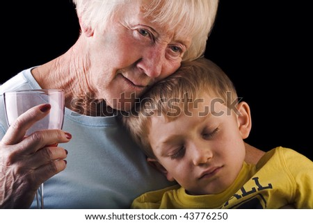 a grandmother cradles her sleeping grandson