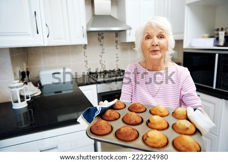A grandmother holding a tray of muffins in the kitchen - stock photo