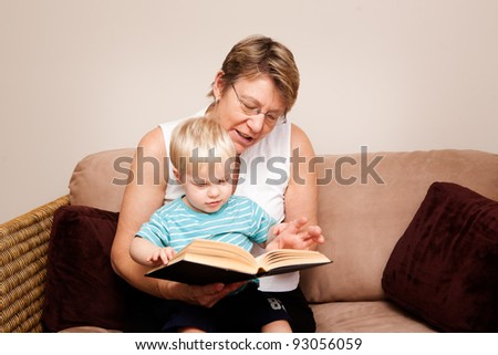 A grandmother, Nanny or au pair reads to a little boy indoors