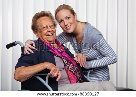 a grandson visiting his grandmother, who is sitting in a wheelchair. - stock photo