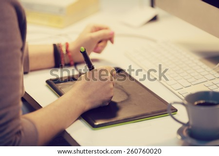 a graphic designer is working and using a graphic tablet - stock photo