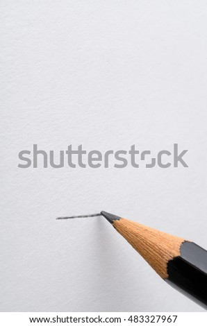 A graphite pencil drawing a line across a blank white page.  Copy space above.