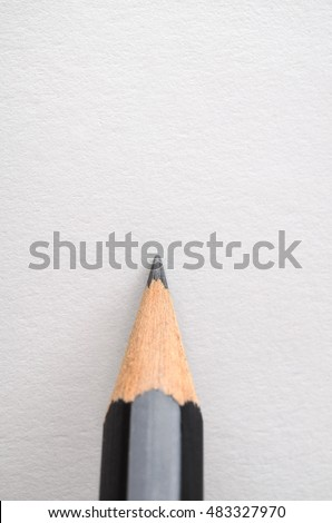 A graphite pencil, poised as if about to write or draw on blank white paper.